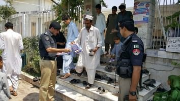 A Pakistani police officer July 1 in Pishtakhara distributes pamphlets to worshippers. The pamphlets ask for public support in improving security. [Javed Khan]