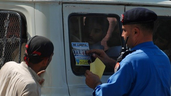 A Peshawar police officer in August 2014 pastes a sticker on a transit van to raise awareness of traffic laws. [Adeel Saeed]