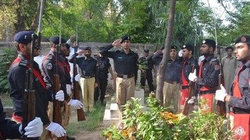 Senior KP Police officers August 4 in Peshawar salute the grave of Superintendent of Police Hilal Haider in observance of KP Police Martyrs' Day. Haider was killed in a suicide bombing in Peshawar in November 2012.  [Javed Aziz Khan]