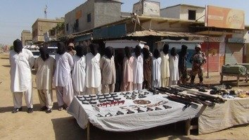 Sindh Rangers August 11 in Karachi display arrested suspects and weapons seized during a combing operation in that city. [Amna Nasir Jamal]
