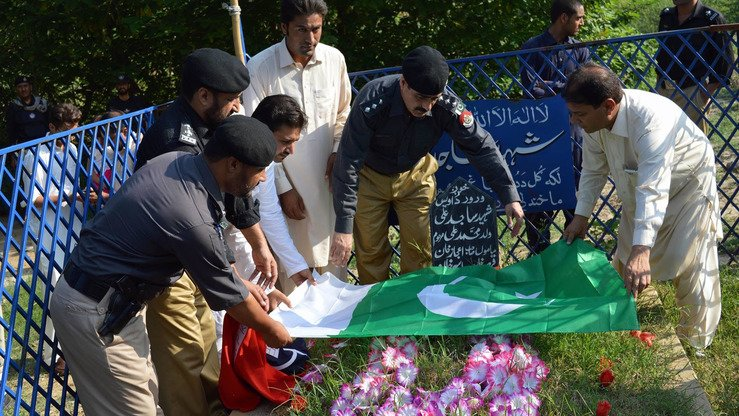 Police officers August 4 in Swabi honour a fallen colleague by placing the Pakistani flag on his grave. President Mamnoon Hussain recently announced gallantry medals for 20 KP police officers, some post-humously. [Javed Khan]