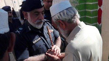 KP Inspector General of Police Nasir Khan Durrani September 2 in Mardan District consoles Lal Badshah on the death of his son, Constable Junaid Khan. Constable Khan gave his life that day in Mardan. [Adeel Saeed]