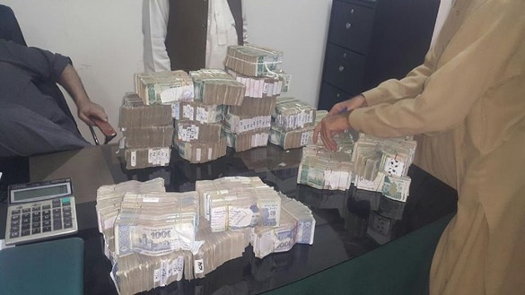 FIA officials in Peshawar November 10, 2015, display currency seized during an anti-money-laundering raid. [Adeel Saeed]