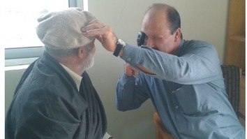 A doctor examines the eyes of a patient in Orakzai Agency in September. [Ashfaq Yusufzai]