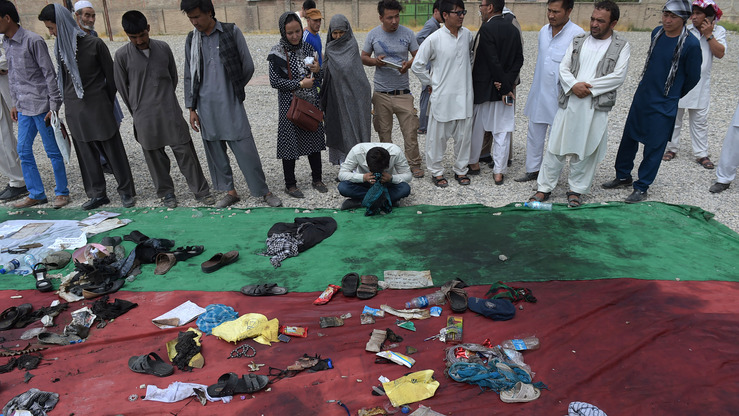 A relative weeps alongside the belongings of those who were killed in a July 23 twin suicide attack at a Shia mosque in Kabul. ISIL took responsibility for the bombing, which killed at least 80 people. [SHAH MARAI/AFP]