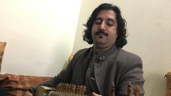 Gulab Khel Afridi plays the rabab, a lute-like instrument, at his academy on December 22. [Syed Ansar Abbas]
