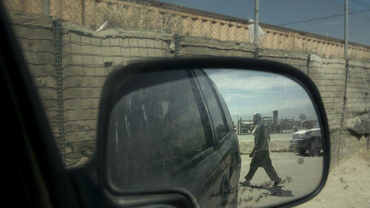 An Afghan labourer is reflected in a vehicle mirror at Bagram Airfield on May 28, 2014. Extremists consider northern Afghanistan an attractive target for extremists because of its proximity to drug-trafficking channels through Central Asia, observers say. [Brendan Smialowski/AFP]