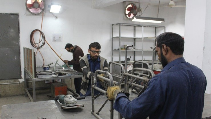 Technicians January 10 in Peshawar build customised wheelchairs to help disabled survivors of terrorism. [Ashfaq Yusufzai]