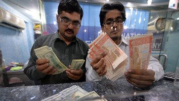 Pakistani currency dealers count rupees and US dollars in Islamabad March 12, 2014. Pakistani authorities are cracking down on terror financing. [AFP/Aamir Qureshi]