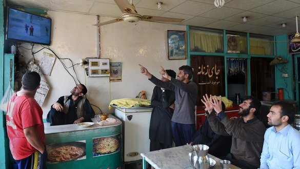 Afghans refugees watch a cricket match in a Peshawar restaurant February 18, 2015. Peshawarites who formerly feared eating out at night are returning to restaurants for dinner after security improved. [A Majeed / AFP]