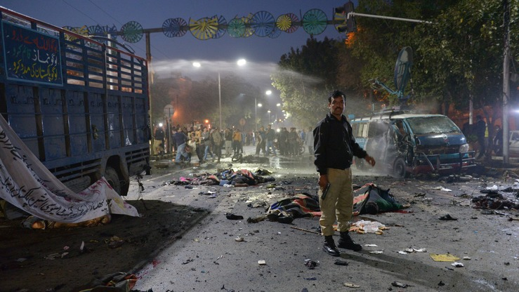 A Pakistani police officer stands alert beside the bodies of victims of a suicide bombing in Lahore on February 13. Tehreek-e-Taliban Pakistan (TTP) faction Jamaat-ul-Ahrar claimed responsibility for the blast, three days after it threatened a series of attacks on government installations throughout the country. [STR/AFP]