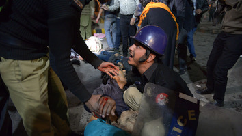 A Pakistani policeman reacts as he attempts to move an injured victim from a blast site in Lahore on February 13. At least 15 people were killed and 87 injured in the blast, according to emergency officials. [Arif Ali/AFP]