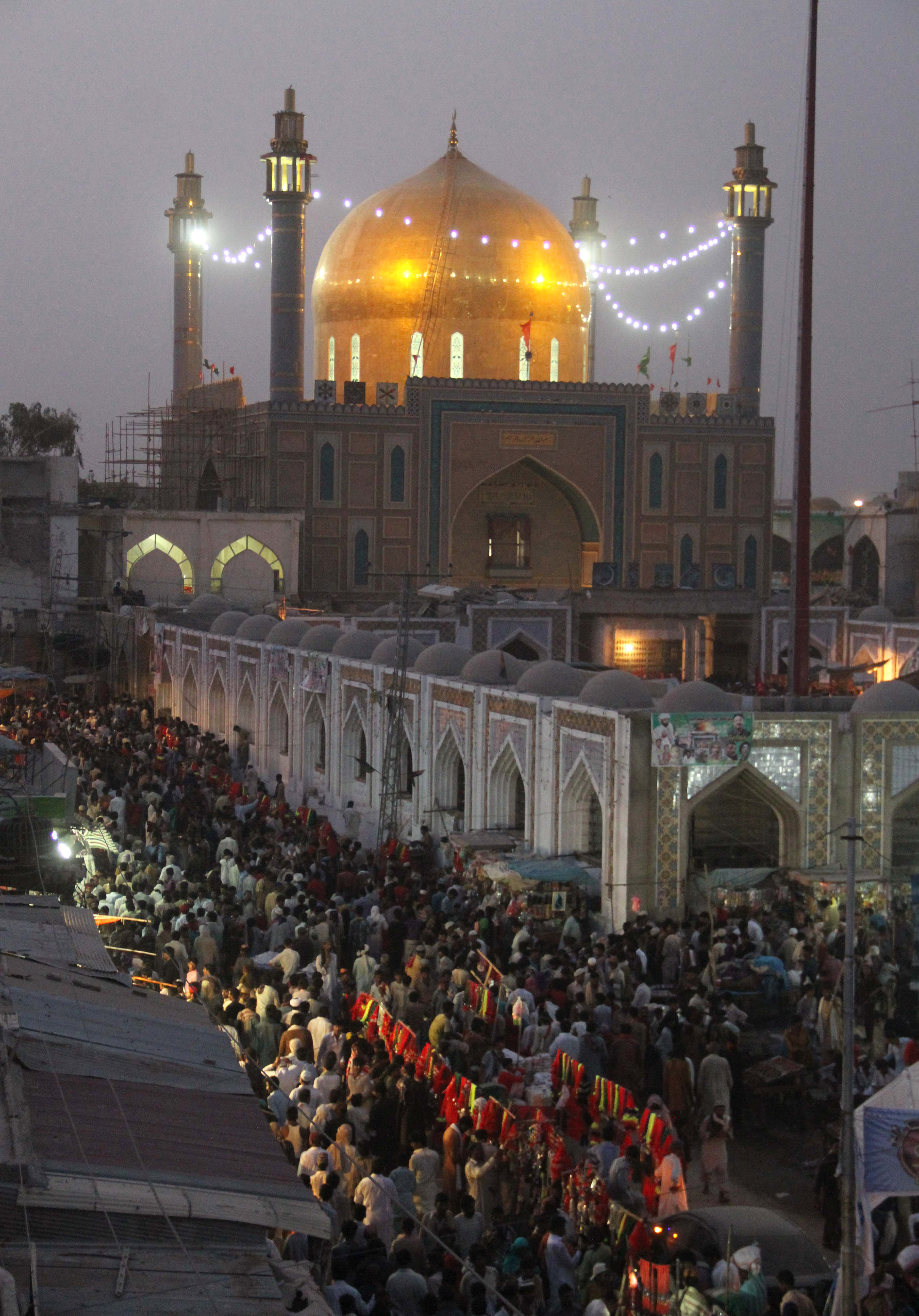 In this photograph taken on June 18, 2014, Pakistani devotees gather at the shrine of 13th century Muslim Sufi saint Lal Shahbaz Qalandar in Sehwan, some 200 kilometres (124 miles) northeast of Karachi, on the anniversary of the saint's death. A bomb ripped through a crowded Sufi shrine February 16 killing dozens. [Yousuf Nagori / AFP]