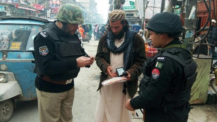 Peshawar policeman check a pedestrian's documents February 18. Pakistan has increased security after a spate of terrorist attacks. [Javed Khan]