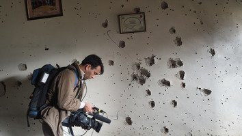 A Pakistani cameraman shoots video in front of a bullet-riddled wall at the Army Public School in Peshawar, a day after a Taliban attack on December 17, 2014, killed 148 people, mostly children. The Pakistan Press Clubs Safety Hub initiative aims to raise awareness of the dangers journalists face in the course of their work and to protect those facing death threats and terrorist attacks. [AFP/Farooq]