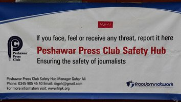 A banner in the Peshawar Press Club urges journalists to report any threats or security concerns. Six press clubs in Pakistan have set up safety hubs to provide security awareness training, protection and assistance to journalists in distress. [Adeel Saeed]