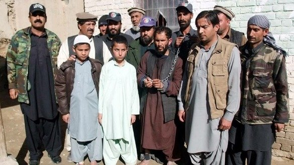 A suspected kidnapper and the two boys whom he allegedly abducted are shown in the custody of Chaman Levies in Qilla Abdullah District, Balochistan, late last year. [Courtesy of Abdul Ghani Kakar]