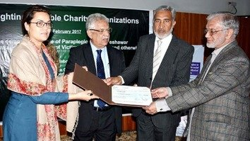 Pakistan Peace Collective (PPC) CEO Bushra Taskeen (left) presents a donation to the Paraplegic Centre in Peshawar February 22. [Pakistan Press Information Department]