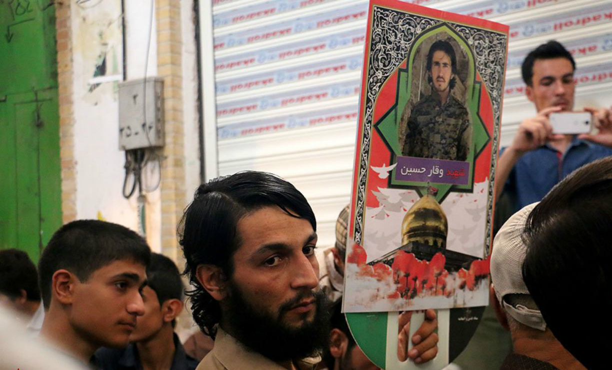 A mourner in Qom, Iran, carries a placard with the name and picture of a Pakistani member of Zainabiyoun Brigade killed in battle in Syria. [File]