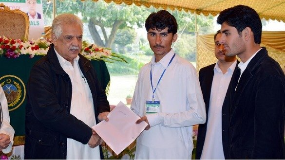 Khyber Pakhtunkhwa Governor Iqbal Zafar Jhagra (left) presents a certificate and cash award to a top student from the Federally Administered Tribal Areas (FATA) March 7 in Peshawar. Jhagra launched an education campaign in April to achieve 100% enrolment in FATA schools. [Courtesy of KP Governor's House]