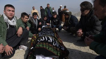 Afghan mourners November 23 in Kabul sit beside the body of a victim of a November 22 mosque bombing. A suicide blast claimed by the 'Islamic State of Iraq and the Levant' (ISIL) targeted a Shia congregation and killed at least 27 people. [Shah Marai/AFP]