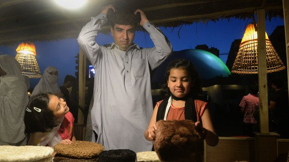 A girl watches her father try on a wool cap at the Peshawar Hunar Mela May 9. [Shahbaz Butt]