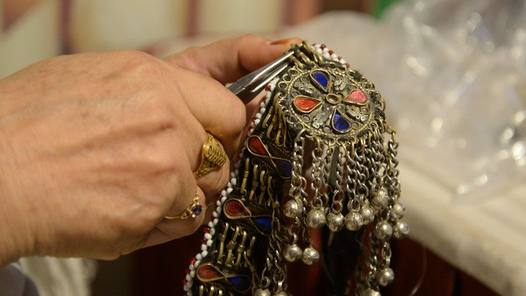 A female jeweller's hand is shown in close-up at the Hunar Mela May 9. [Shahbaz Butt]