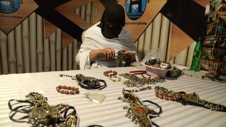 A woman crafts jewellery at the Hunar Mela May 9. [Shahbaz Butt]