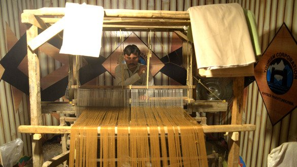 A tailor weaves clothing through a traditional loom at the Hunar Mela May 9. [Shahbaz Butt]
