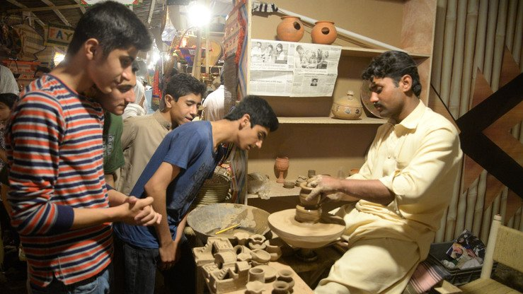 A potter makes earthenware toys at the Hunar Mela May 9. [Shahbaz Butt]