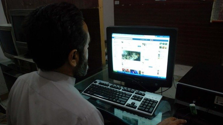 A man looks at his social media accounts in Peshawar on May 16. Pakistan is taking measures to stop terrorists and banned organisations from recruiting unwitting youth online. [Muhammad Shakil]