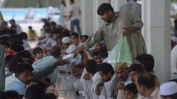 A Pakistani volunteer serves Iftar food to Muslim devotees preparing to break their fast at Faisal Mosque in Islamabad on June 17, 2016 during the holy fasting month of Ramadan. [Aamir Qureshi/AFP]