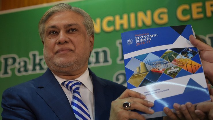 Finance Minister Ishaq Dar holds a copy of the 'Pakistan Economic Survey 2016-17' report during in Islamabad May 25. [Aamir Qureshi/AFP]