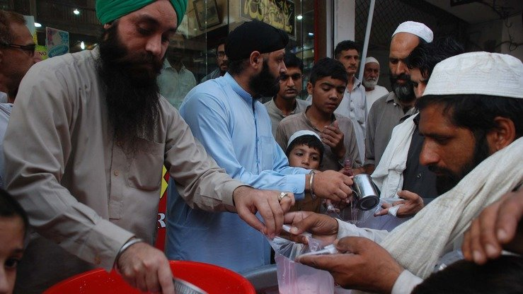 Sahib Singh (left)  and his brother Nam Singh distribute a sweet drink to fasting Muslims June 2 in Peshawar. [Adeel Saeed]