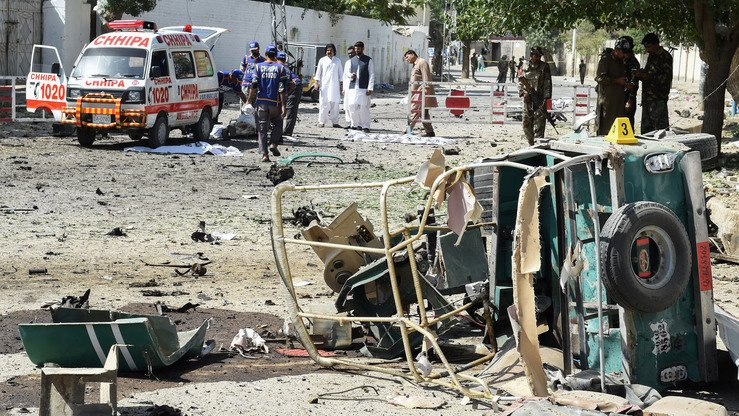 Pakistani medics June 23 in Quetta move a victim's body at the site of a bombing that targeted a police vehicle that day. The blast killed at least 13 people, said officials. [Banaras Khan/AFP]