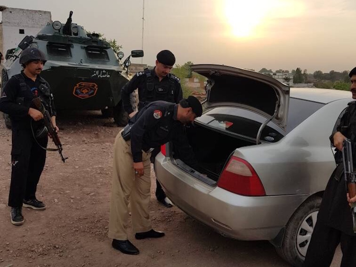 Police officers in Badhaber search a car at an entry point to Peshawar June 20. Authorities beefed up security at all entry points and within the city ahead of Eid ul Fitr. [Javed Khan]