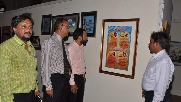 Some art admirers focus on a painting at the exhibition June 19. [Javed Mahmood]