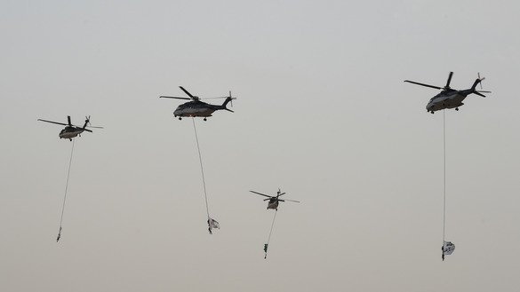 A picture taken on May 23rd shows Saudi military helicopters performing at a graduation ceremony, demonstrating counter-terrorism tactics, at the Special Forces College in Riyadh. [Fayez Nureldine/AFP]