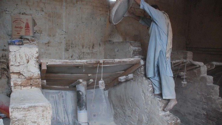 A worker pours wheat into the hopper for grinding by wheel-shaped stones moving in a circle. [Adeel Saeed]