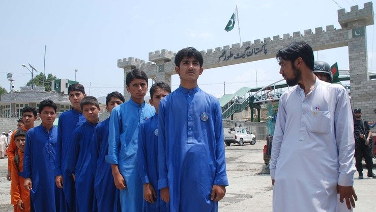 Afghan schoolboys wait in line for identification verification at the Torkham border post July 19. [Muhammad Shakil]