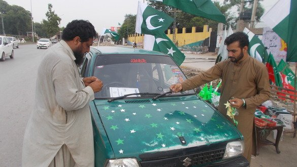 Two men decorate a car in Peshawar August 4 in preparation for Pakistan's Independence Day, August 14. [Ashfaq Yusufzai]