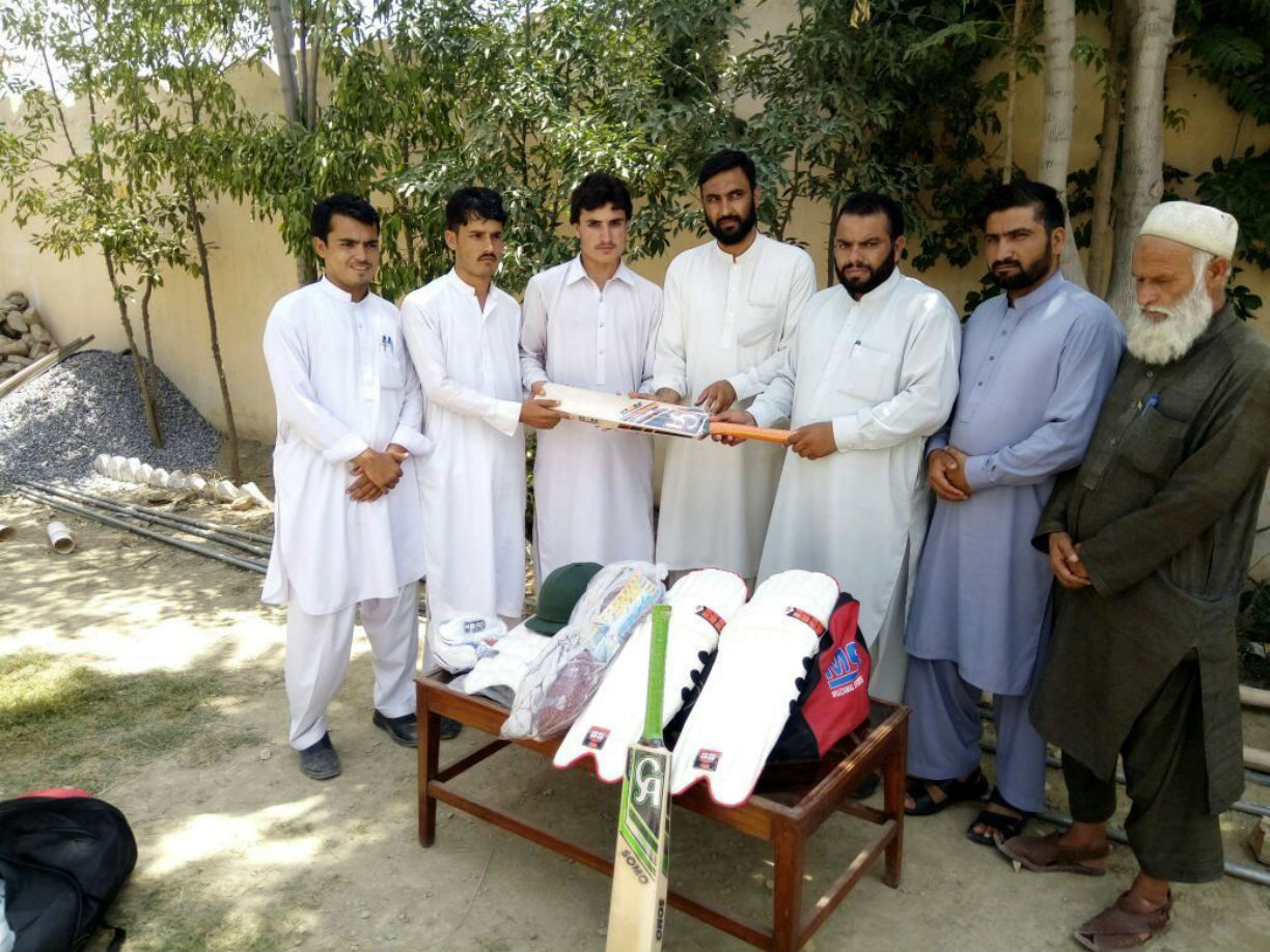 Rahid Gul Malagori (third from right), agency sports manager of Khyber Agency, August 2 in Landi Kotal poses with the Landi Kotal cricket team and sports kits intended for them. A local official (wearing blue) and a local elder (beard) look on. [Danish Yousafzai]