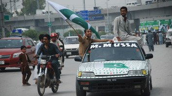 A man waves the Pakistani flag as part of Independence Day celebrations in Peshawar on August 14. [Muhammad Shakil]