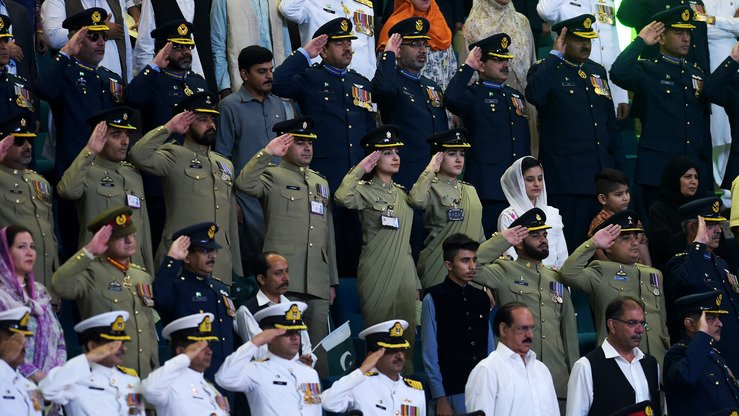 Pakistani military officers salute as they hear the national anthem after hoisting the country's flag to celebrate Independence Day in Islamabad August 14. [Aamir Qureshi/AFP]