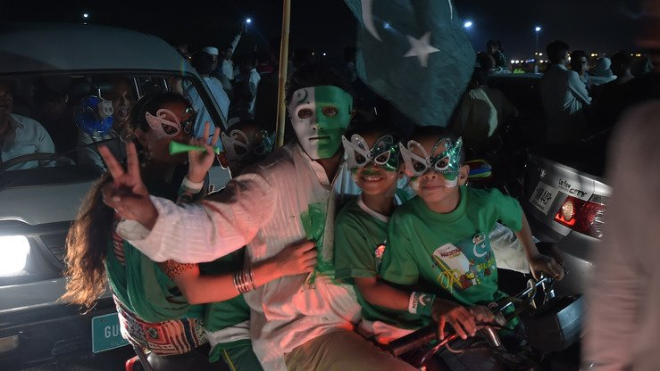 Youths wear masks as they march through Islamabad August 13 to mark Independence Day. Pakistan August 14 celebrated its 70th anniversary of its independence from British rule. [Aamir Qureshi/AFP]