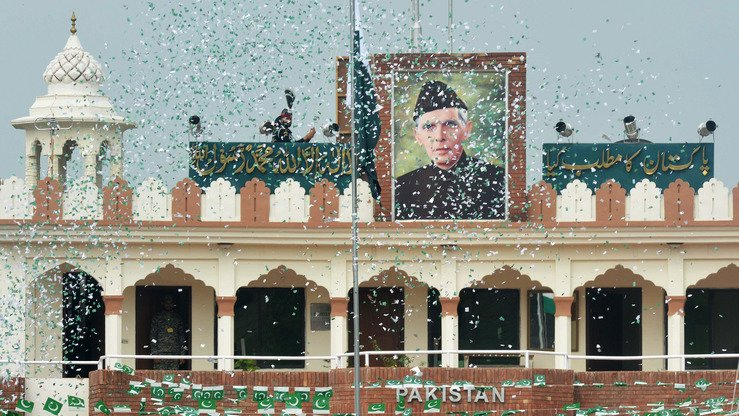 The portrait of Muhammad Ali Jinnah is seen at at the India-Pakistan Wagah border post as a Pakistani Ranger (top) unfurls the Pakistani national flag to celebrate Independence Day August 14. Jinnah was the founder of Pakistan, which gained independence from Great Britain 70 years ago. [Narinder Nanu/AFP]