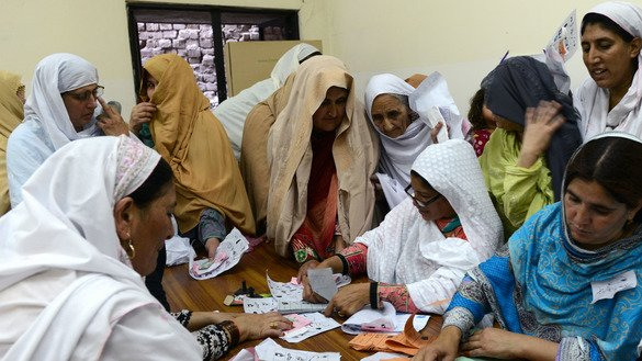 Pakistani women gather around the presiding officers of a local election body in Peshawar May 30, 2015. Khyber Pakhtunkhwa is seeking to enact laws to benefit women. [AFP/A Majeed]