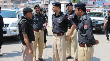 Capital City Police Officer Mohammad Tahir (centre) talks to policemen deployed in Peshawar August 29. [Javed Khan]