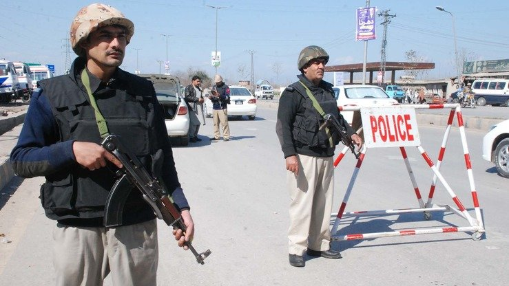 Police officers guard a barricade in Peshawar in February. [Adeel Saeed]