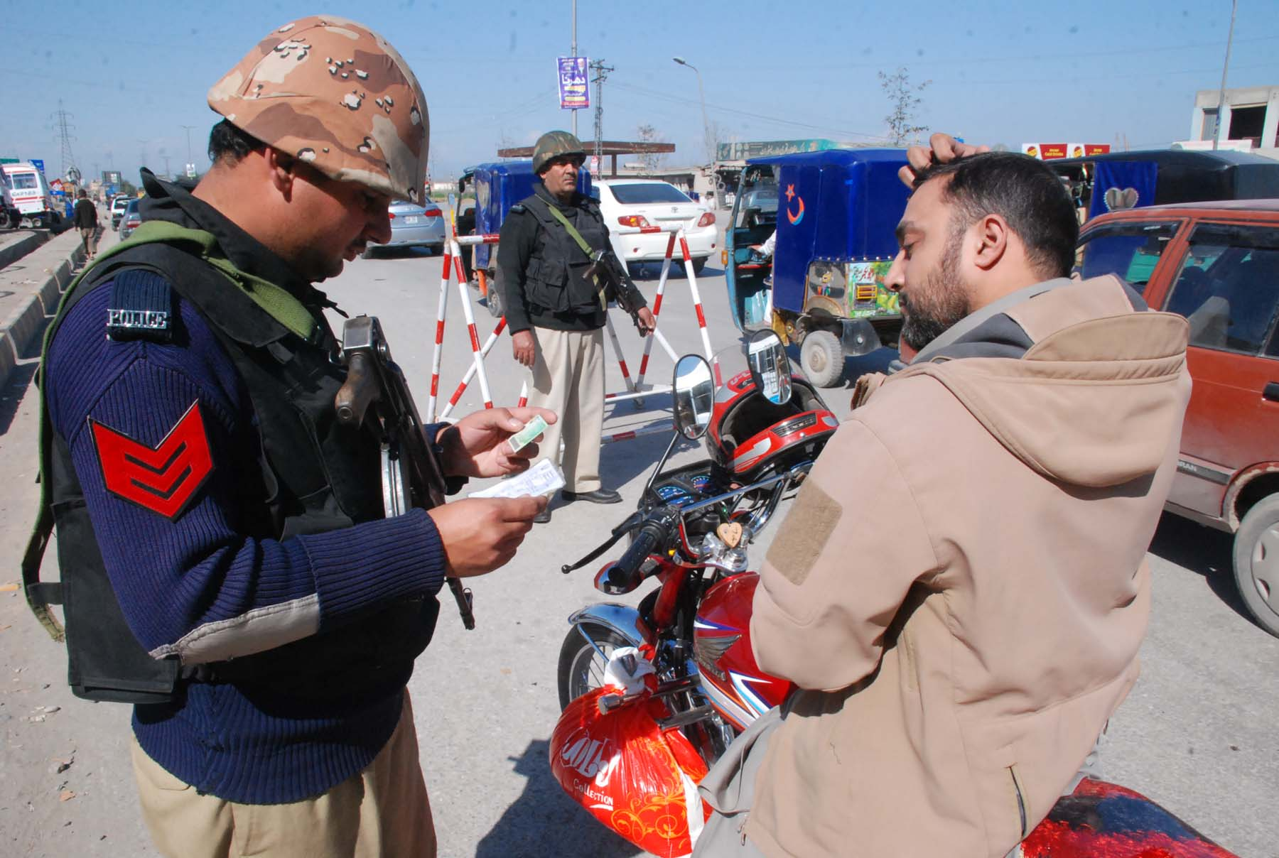 A police officer examines a motorcyclist's documents in Peshawar in February. [Adeel Saeed]